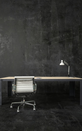 Dark room with lamp on empty desk and white office chair on wheels. Walls and the floor is matte black. Copy space