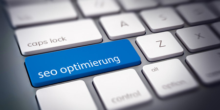 SEO Optimierung - SEO Optimization - concept of a business website with German text on a single blue computer key on a white a white keyboard Banque d'images - 124741932