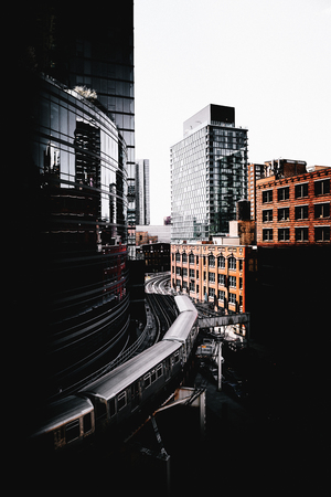 Train turning between business buildings in downtown Chicago, viewed from high angle. Darkened urban cityscape with modern architecture and old red brick building Banque d'images - 124741948