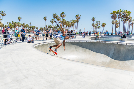 LOS ANGELES, USA - May 15 2018: People watching a skilled young man practicing extreme skateboarding in a modern skate park in Los Angeles, California, USA 新聞圖片