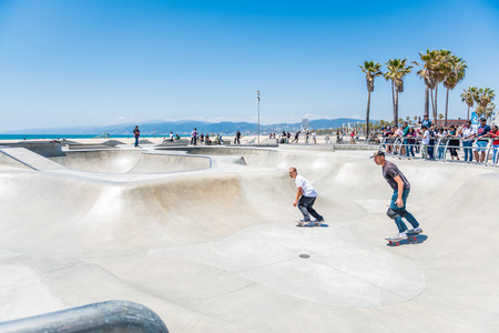 LOS ANGELES, USA - May 15 2018: Two American young men skating together in a cool skate park with modern equipment in Los Angeles, California, USA