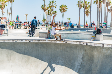LOS ANGELES, USA - May 15 2018: Young skateboarder performing a balancing stunt on his skateboard along the edge of an outdoor skating rink at Venice Beach, Santa Monica, Los Angeles, California