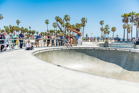 LOS ANGELES, USA - May 15 2018: Venice Beach outdoor skate park with skateboarders and a group of people watching them perform stunts in Santa Monica, Los Angeles, California