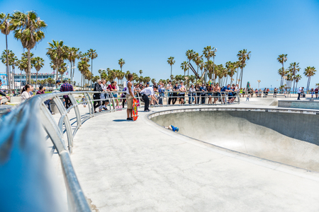 LOS ANGELES, USA - May 15 2018: People standing watching skateboarders at a skate park at the waterfront in Venice Beach,Santa Monica, Los Angeles, California