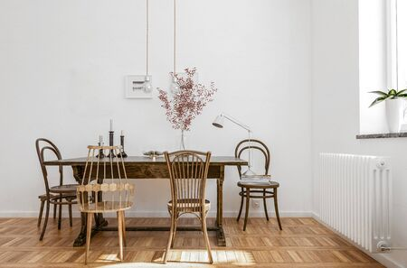 Interesting dining table with mixed design bentwood chairs in a corner alongside a radiator on a polished parquet floor. 3d rendering Banque d'images - 130167310