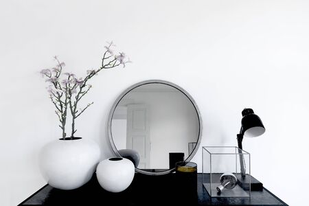 Close up on mirror and plant pots next to lamp and metal trinket in transparent box on modern black table. 3d rendering