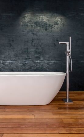 Modern white boat-shaped bathtub with tall chrome faucet on wooden floorboards in front to a textured grey wall. 3d rendering Banque d'images - 130167332