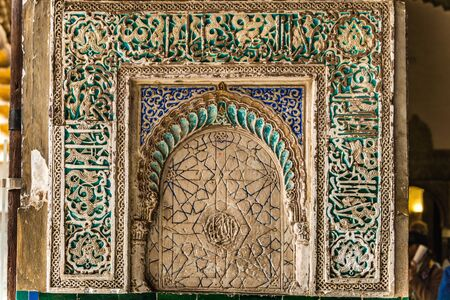 SEVILLE, SPAIN - December 09 2019: Detail of an ornate carved tiled panel in the Real Alcazar palace in Seville, Spain a popular tourist attraction and Unesco listed site 新闻类图片