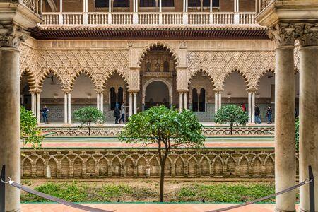 SEVILLE, SPAIN - December 09 2019: Patio de las Doncellas courtyard, Real Alcazar, Seville Spain viewed between columns, a Unesco World Heritage Site 新闻类图片