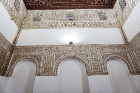 SEVILLE, SPAIN - December 09 2019: White walls with ornamented arches inside the famous Spanish palace of royal Alcazars of Seville