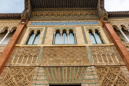SEVILLE, SPAIN - December 09 2019: Moorish windows in Patio de la Monteria courtyard in the Real Alcazar in Seville Spain looking up from below with decorative frieze, a Unesco World Heritage Site 新闻类图片