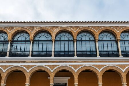 SEVILLE, SPAIN - December 09 2019: Row of arched windows in Patio de la Monteria courtyard exterior facade in Real Alcazar Royal residence in Seville, Spain