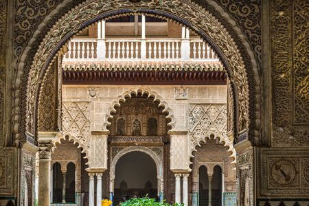 SEVILLE, SPAIN - December 09 2019: View through an arch of Patio de las Doncellas or Hall of the Maidens in the Real Alcazar, Seville, Spain, a UNESCO World Heritage Site 新闻类图片