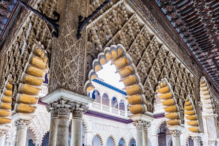SEVILLE, SPAIN - December 09 2019: Detail of the architecture surrounding the Patio de las Doncellas courtyard in the Real Alcazar Spanish Royal Residence in Seville Spain with a closeup on the decoration of the arches and ceiling 新闻类图片