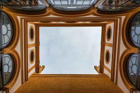 SEVILLE, SPAIN - December 09 2019: Looking up to the sky from an inner courtyard in Real Alcazar, Seville, Spain in a symmetrical view of arched and circular windows 新闻类图片
