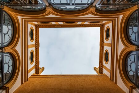 SEVILLE, SPAIN - December 09 2019: Sky view from inside the narrow courtyard in the old palace of Royal Alcazar of Seville, Spain. Arched and round windows and brown walls and cloudy sky above