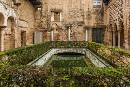 SEVILLE, SPAIN - December 09 2019: Patio del Yeso courtyard in Real Alcazar, Seville, Spain with remnants of Almohad Moorish architecture 新闻类图片