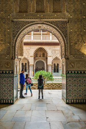 SEVILLE, SPAIN - December 09 2019: Young family viewing the Real Alcazar palace in Seville standing under an arch opening to the Patio de las Doncellas courtyard