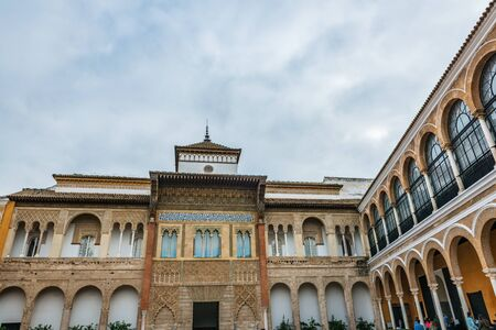 SEVILLE, SPAIN - December 09 2019: Upper floor of Patio de la Monteria courtyard with its arched windows in the Real Alcazar, a Spanish Royal Residence in Seville