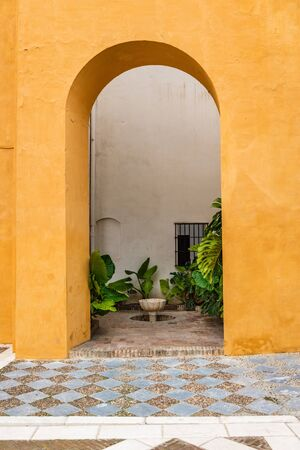 SEVILLE, SPAIN - December 09 2019: Arch leading through a colorful orange wall to enclosed courtyard garden with green plants and small water feature in Real Alcazar, Seville, Spain Sajtókép