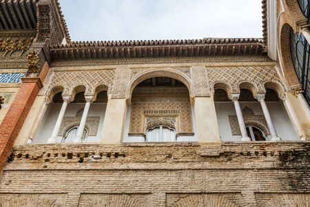 SEVILLE, SPAIN - December 09 2019: Exterior facade and windows in the Patio de la Monteria courtyard, or Hunters courtyard in the Real Alcazar palace in Seville Spain