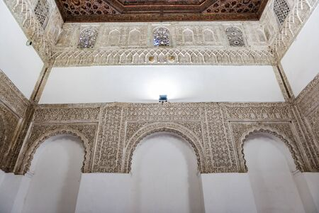 SEVILLE, SPAIN - December 09 2019: Ornamented arches of the white walls of Patio Del Yeso in the old Arab Palace in Seville, Spain