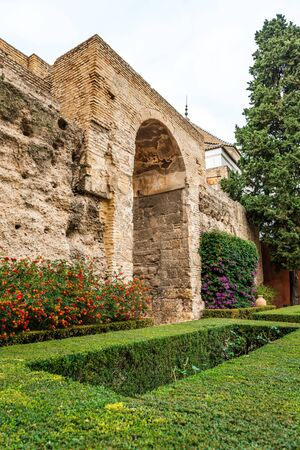 SEVILLE, SPAIN - December 09 2019: Garden with colorful flowering plants and neat green lawn and massive stone wall at Real Alcazar royal palace in Seville, Spain a popular tourist attraction 新闻类图片