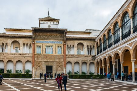 SEVILLE, SPAIN - December 09 2019: Tourists sightseeing in the Real Alcazar, Seville, Spain in the Patio de la Monteria courtyard under a cloudy sky