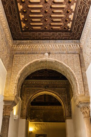 SEVILLE, SPAIN - December 09 2019: Ornamented arches and ceiling of the corridor inside the Royal Alcazars of Seville castle in Spain. Famous Andalusian architecture 新闻类图片