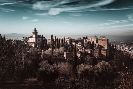 Dark moody atmospheric landscape of the Alhambra Palace a Moorish fortress in Granada, Andalusia, Spain overlooking the city 新闻类图片