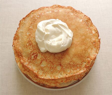 Ruddy pancakes with sour cream on a plate.