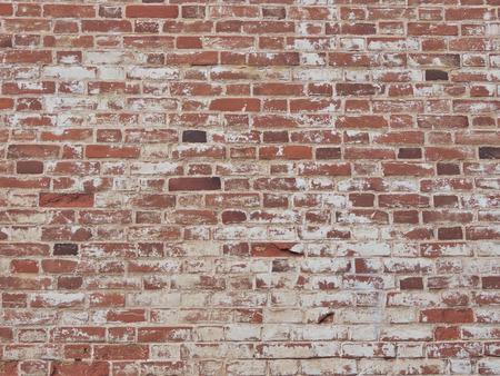 Oude rode bakstenen muur met een sjofele verf. Bakstenen achtergrond.