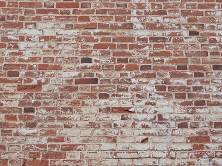 Old red brick wall with shabby paint. Brick background.