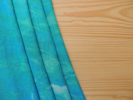pareo: Turquoise folded the pareo textile on wooden background.