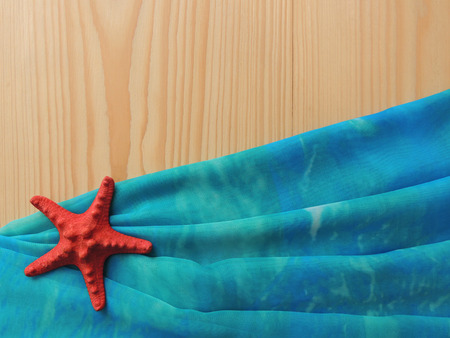 pareo: Composition of marine turquoise fabric folded pareo with sea star on wooden background.