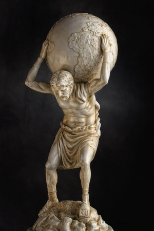 A resin statue replica of the titan Atlas of Greek mythology carries the weight of the heavens on his shoulders   Dramatic lighting help accentuate the detail in the torso and legs