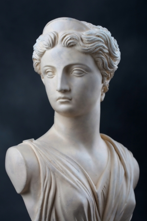 greek statue: A copy of a stone bust of the Greek Goddess Artemis, daughter of Zeus, twin sister of Apollo   This photograph provides a 2 3 view of the face and has dramatic low key lighting