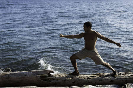 Young black man in warrior pose on log at beach with small wave in background  photo