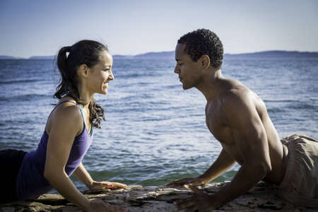 Close up of young couple on beach, facing each other in Cobra yoga pose with water in background Stock Photo