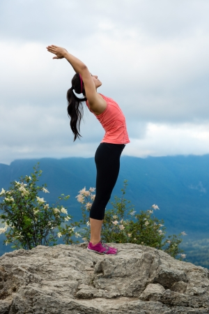 Young woman in yoga pose on top of mountain with beautiful vista in background. photo