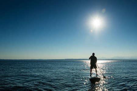 Man paddling stand up paddle board