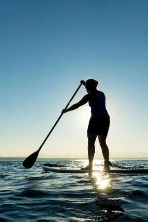 paddle: Woman paddling stand up paddle board