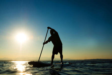 Man paddling stand up paddle board