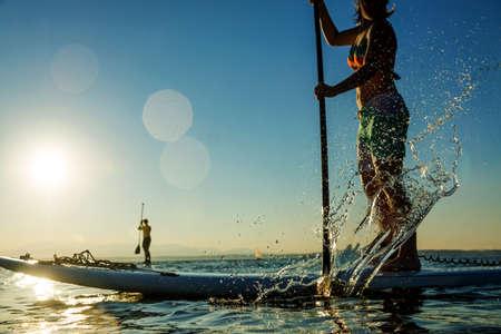 Mujer remando de pie bordo de paddle