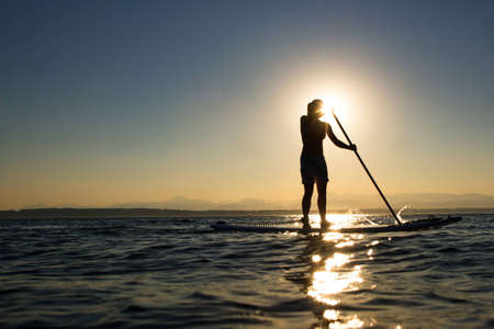 board: Woman paddling stand up paddle board