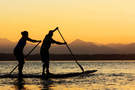 active couple: Couple paddling stand up paddle boards