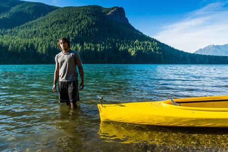 Black man standing in shallow water next to yellow kayak. photo