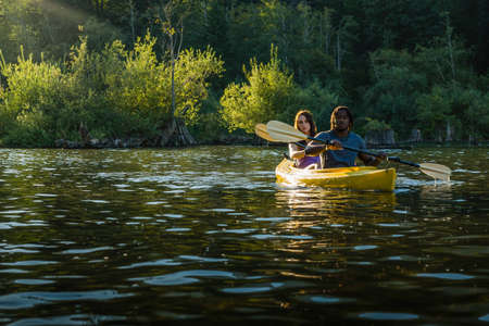 Couple paddling in kayak on lake. photo