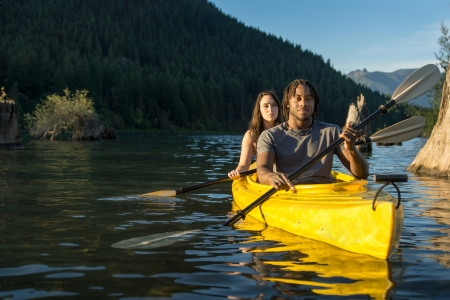 paddling: Couple paddling in kayak on lake. Stock Photo