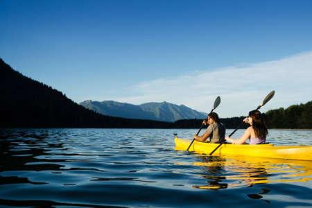 jezior: Para wiosłowania w kajaku na jeziorze. Zdjęcie Seryjne